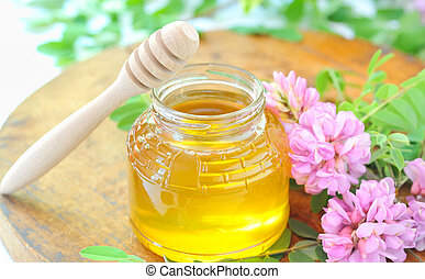 jar full of honey and stick with acacia pink and white flowers