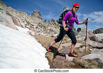 Hiking woman in mountains with snow