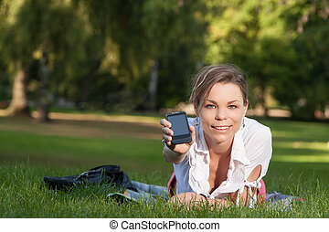 Young, attractive woman shows her smartphone - Young,...