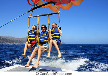 Happy Family Parasailing - Father and Twin Daughters...