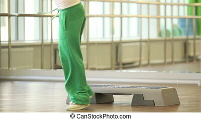 On step board  - Woman training on step board in sport gym