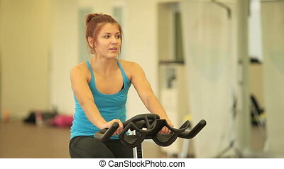 Training on cycle - Sporty woman training on cycle in sport...