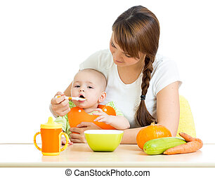 young mother spoon feeding her baby boy isolated on white -...