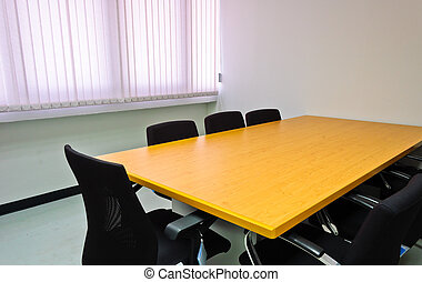 Small meeting room with wooden table and black chairs