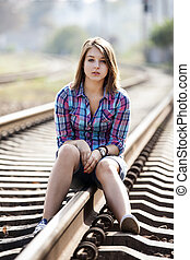 Sad teen girl sitting at railway