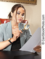 adviser - business woman looks on one document by magnifying...