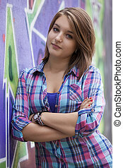 Style teen girl standing near graffiti wall
