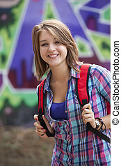 Style teen girl with backpack standing near graffiti wall.