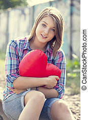 Teen girl with heart at outdoor