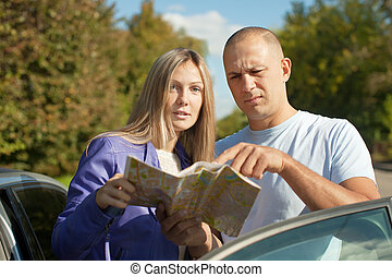 couple looking at the map on the road - Traveler couple...
