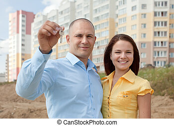 happy family in front of new home - happy young family with...