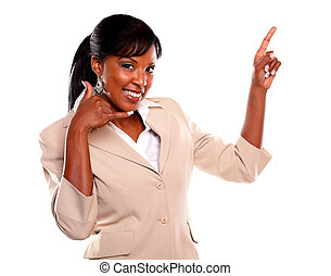 Charming businesswoman pointing up looking at you