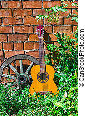 Guitar and the old wagon wheel against a brick wall