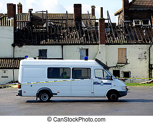 Crime Scene Fire Damaged House with police van outside