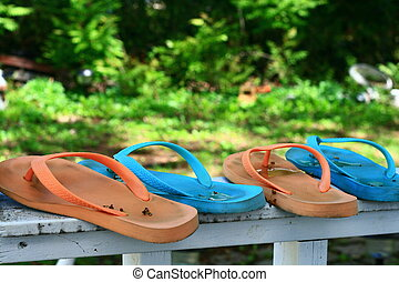 flip flops - flip flop drying on a fence railing after the...