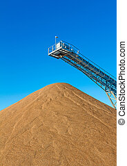 Conveyor surface workings - Conveyor belt and gravel heap at...