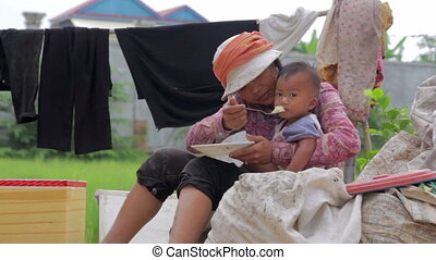 Mother feeding baby in slums