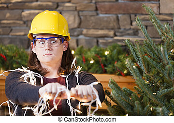Holiday safety - Young woman wearing hardhat and safety...