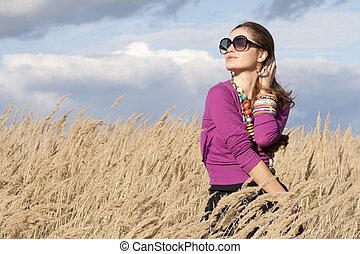 Young woman wearing jewellery and sunglasses looking aside