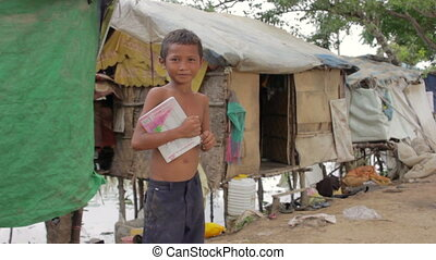 Boy in slum holding book