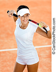 Woman keeps tennis racquet and ball on her shoulders - Woman...