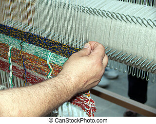 weaving a carpet - a man weaving a carpet in a laboratory in...