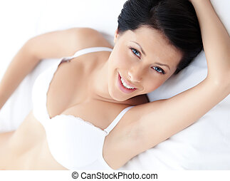 Woman in underwear is lying in the bed with white bed linen...
