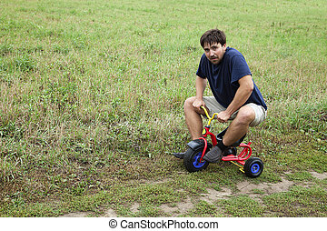 Adult man on a small tricycle - Adult man tying to ride on a...