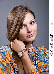 Portrait of a young beautiful girl with hand clock