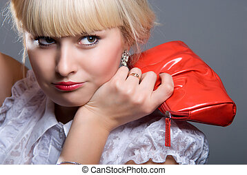 Close-up portrait of fashion model holding purse on gray...