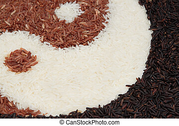 close up pile of brown rice and jasmine rice in yin-yang...