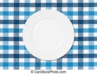 White plate on blue and white tablecloth background