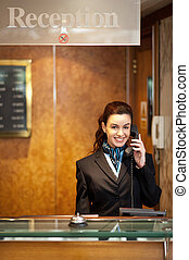 Attractive young receptionist receiving calls - Attractive...