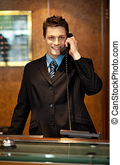 Cheerful front desk executive attending phone call while...