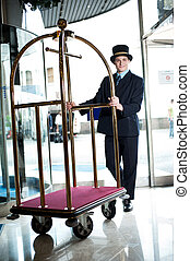 Profile shot of a doorman holding a cart