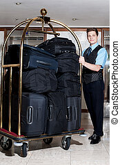 Concierge with a pile of bags in luggage cart - Handsome...