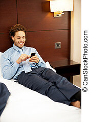 Man resting in luxurious bed and messaging his friends and...