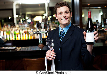 Cheerful executive posing with a bottle of wine