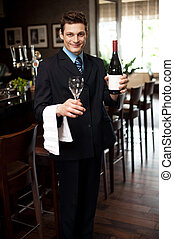 Man posing with a bottle of wine in restaurant