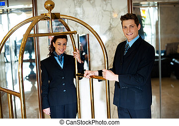 Concierges holding the cart and posing in front of the...