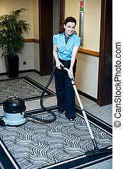 Staff cleaning carpet with a vacuum cleaner. Smiling and...