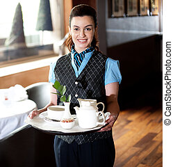 Pretty waitress posing with tea for guests in the restaurant