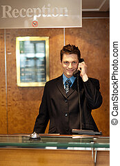 Profile shot of a handsome receptionist on the phone posing...