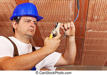 Worker installing electical wiring in a new building -...