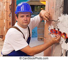 Installing electrical wires - Worker installing electrical...
