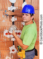 Installing electrical wires - electician working