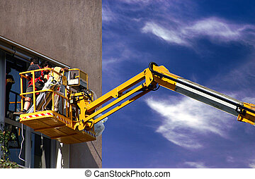 Worker on a high lift - Worker on a yellow high lift
