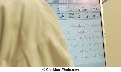 Heart attack Patient stand next to heart monitor with EKG...