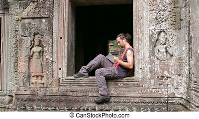 tourist reading book in angkor