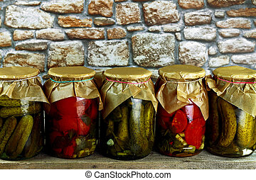 Pickled vegetables - Jars with pickled green cucumbers and...